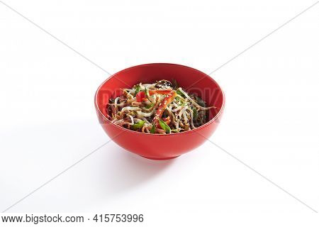 Udon noodle with teriyaki chicken and vegetable. Asian style noodle food on white background. Teriyaki chicken noodle in red bowl with sesame and onion