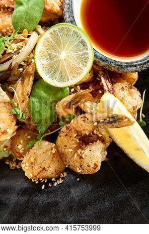 Teppanyaki Style Seafood - Grilled Mixed Seafood with Soy Sauce and Vegetables. Japanese Teppanyaki Salmon Steak, Shrimp, Scallop and Fish Fillet garnished with lemon and green salad. Top view