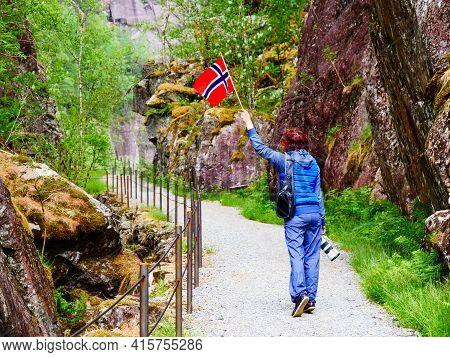 Tourist Woman With Norwegian Flag And Camera Walking Trough Mountains Path In Allmannajuvet Area Sau