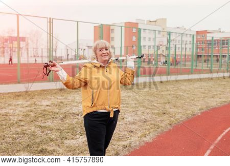 An Elderly Woman In A Yellow Jacket With A Scandinavian Stick Held Behind Her Back Stands At The Sta