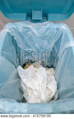 Closeup Of The Many Used Toilet Paper In The Plastic Bag On The Trashcan Near The White Wall, Before
