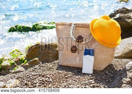 Beach Bag With A White Tube Of Sunscreen On A Pebble Beach Near The Sea. Travel, Beach Holiday At Th