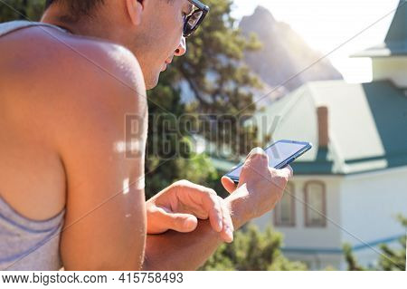 A Male Tourist Uses A Smartphone While Traveling. Navigation, Sightseeing Search, Mobile Roaming, On
