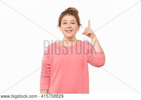 Pretty Teen Girl With Hair Bun Showing Index Finger, Says: I Have An Idea, Isolated On White Backgro