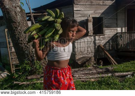 Sandy Bay, Nicaragua. 03-15-2019. Girl Is Walking Carrying Bananas On Her Back On Her Way Home In Th