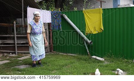 80s Great-grandmother In Authentic Rural Clothes Stand Near Laundry Hanging On Clothesline To Dry Ou