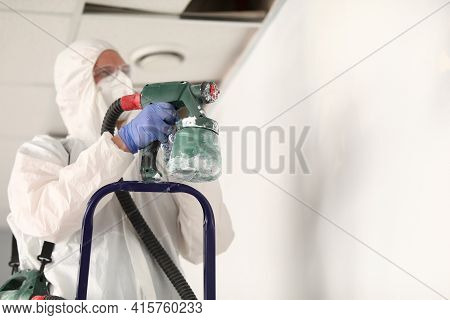 Master Painter In Protective Suit Is Touching Wall With Spray Gun