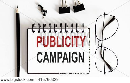 Publicity Campaign Notepad Writing On White Background With Pencil And Glasses