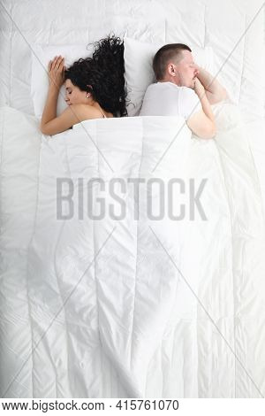 Man And Woman Sleep In Bed, Facing Away From Each Other