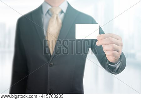 Hand Holding Blank Business Card. Handsome Businessman In Black Suit Showing His Mockup Credit Card