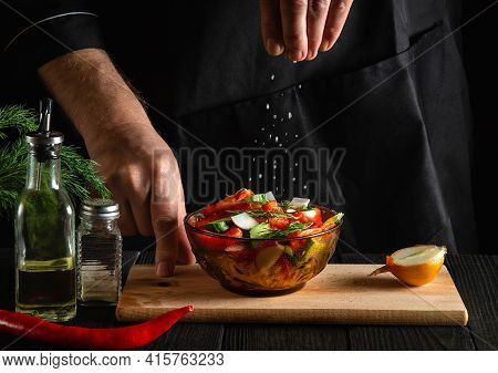 The Chef Sprinkles Salted Fresh Vegetable Salad In Plate On A Wooden Table. Cooking Healthy Food In