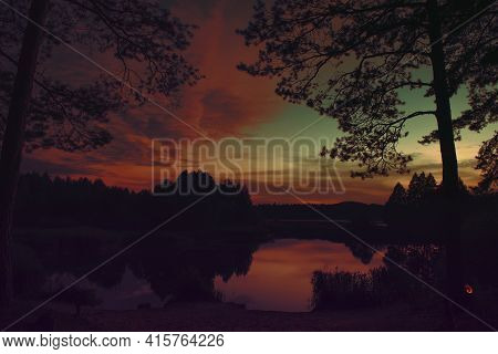 A Forest Lake Hidden In A Dense Forest Thicket. Sunset, The Last Rays Of The Sun Before Darkness. Th