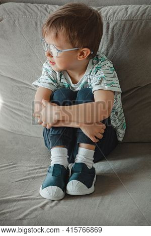 Child With Autism In Glasses Sits On The Sofa And Is Sad
