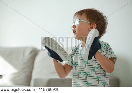 Child With Autism In Glasses Play With His Shoes