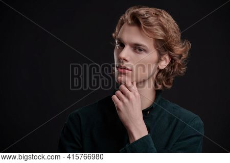 Portrait of a handsome young man with wavy blond hair posing on a black background. Men's beauty.