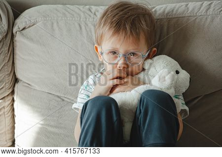 A Child With Autism In Glasses Sits On The Sofa And Sad, Hug A S