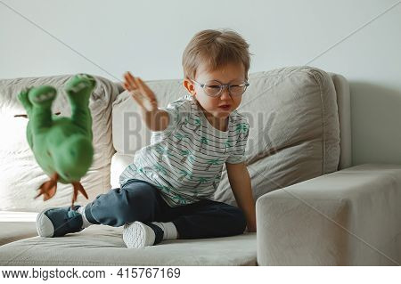 A Child With Autism In Glasses Sits On The Sofa And Sad, Angry A