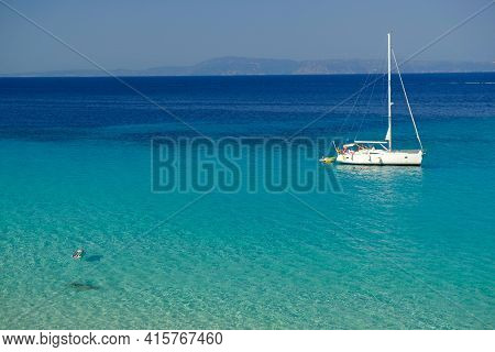 Chalkidiki, Greece - August 14, 2017 : A Sailboat And A Single Person Swimming In The Crystal Clear