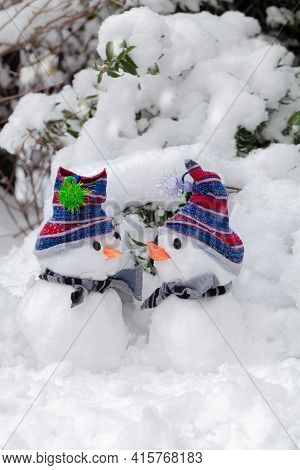 Two Cute Little Snowmen In A Snow Winter Scene Huddled Together. Dressed With Hats And Scarfs And Ca