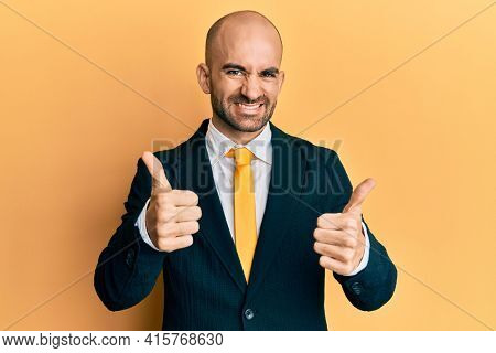 Young hispanic man wearing business suit and tie approving doing positive gesture with hand, thumbs up smiling and happy for success. winner gesture.