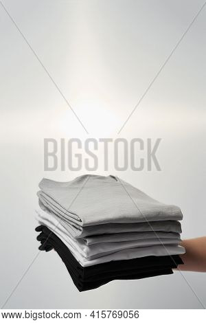 Comfort And Easy Wear. Male Hand Holding Stack Of Multi Colored T-shirts Againtst Grey Background. C