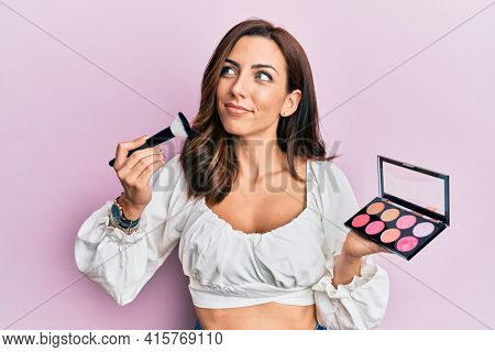 Young brunette woman holding makeup brush and blush smiling looking to the side and staring away thinking.