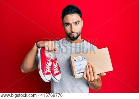 Young man with beard taking casual red shoes from box skeptic and nervous, frowning upset because of problem. negative person.