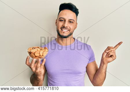 Young arab man holding bowl of salty crackers biscuits smiling happy pointing with hand and finger to the side