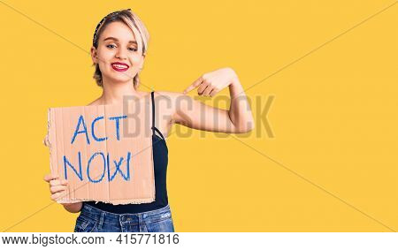 Young beautiful blonde woman holding act now banner pointing finger to one self smiling happy and proud