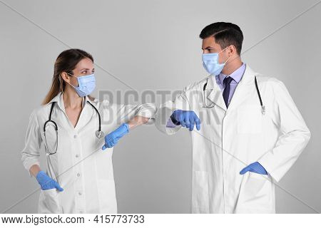 Doctors Greeting Each Other By Bumping Elbows Instead Of Handshake On Light Grey Background