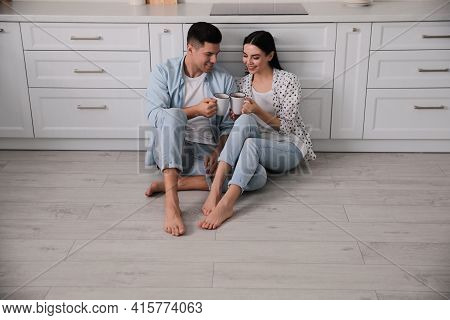 Happy Couple Sitting On Warm Floor In Kitchen. Heating System