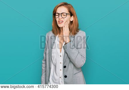 Young caucasian woman wearing business style and glasses touching mouth with hand with painful expression because of toothache or dental illness on teeth. dentist