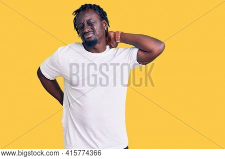 Young african american man with braids wearing casual white tshirt suffering of neck ache injury, touching neck with hand, muscular pain