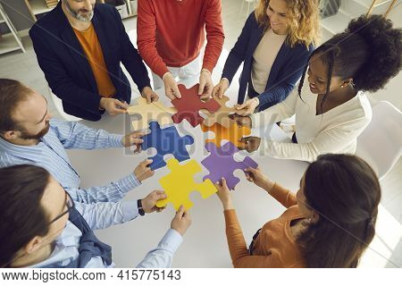 Business Team Connecting Puzzle Parts As Metaphor For Teamwork, Cooperation And Finding Solution