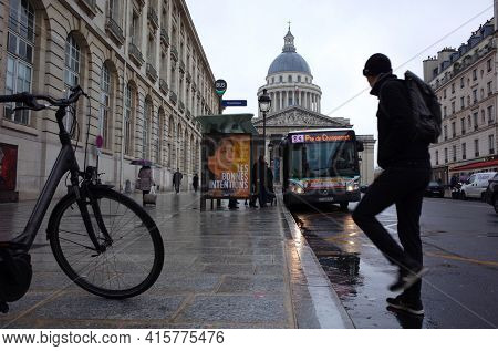 Paris, France - November 20, 2018: Street photo, Casual passerby in black, bicycle, bus stops at Pantheon station, Parisian street in rainy day, Neoclassical architecture