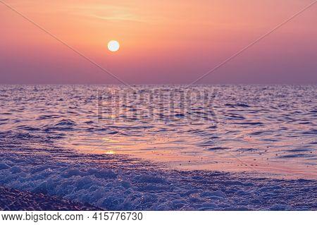 Vivid Sunset Over The Sea Water Splash.  Evening Peaceful Landscape With Summer Beach. Defocused Pho