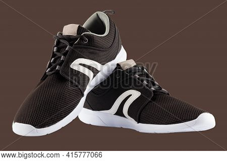 Pair Of Black Airmesh Summer Walking Lightweight Shoes Isolated On Brown Background
