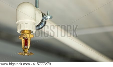 Close Up Image Of Fire Sprinkler With Fire In Background. Fire Sprinklers Are Part Of An Integrated