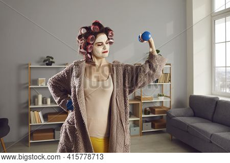 Funny Woman In Skincare Face Mask And Hair Curlers Doing Exercise With Dumbbells At Home