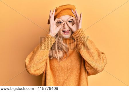 Beautiful young caucasian girl wearing french look with beret doing ok gesture like binoculars sticking tongue out, eyes looking through fingers. crazy expression.
