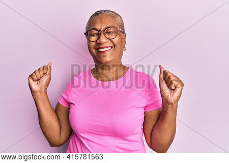 Senior african american woman wearing casual clothes and glasses very happy and excited doing winner gesture with arms raised, smiling and screaming for success. celebration concept.