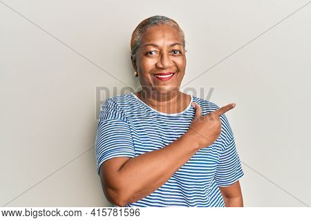Senior african american woman wearing casual clothes smiling cheerful pointing with hand and finger up to the side
