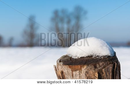 Wooden Pole With Melding Snow On The Top