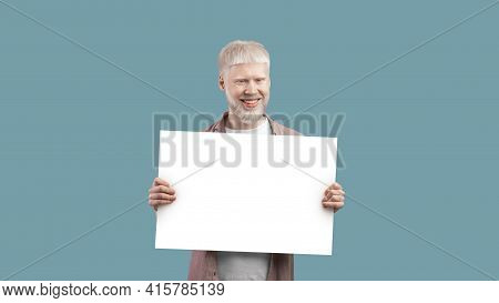 Look Here. Excited Albino Man Holding Blank Poster With Copy Space On Studio Background, Panorama, F