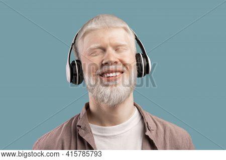 Music Lover. Peaceful Albino Man In Wireless Headphones Listening Audio On Turquoise Studio Backgrou