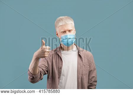 Stay Safe. Albino Man In Medical Protective Mask Showing Thumb Up On Studio Background