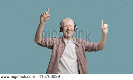 Happy Albino Man Enjoying Music In Wireless Headphones, Dancing And Raising Fingers Up Over Turquois