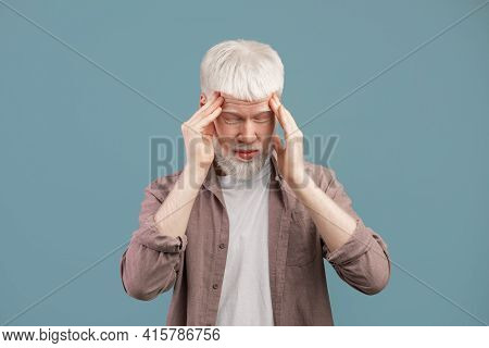 Exhausted Young Albino Man Suffering From Headache, Rubbing Temples With Closed Eyes On Blue Studio