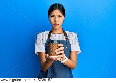 Young chinese woman wearing waiter apron holding cup of coffee skeptic and nervous, frowning upset because of problem. negative person.