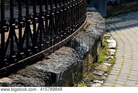 Paved Granite Cube Path In The Park. Footpath And Fenced With A Formal Gray Metal Fence. Separating